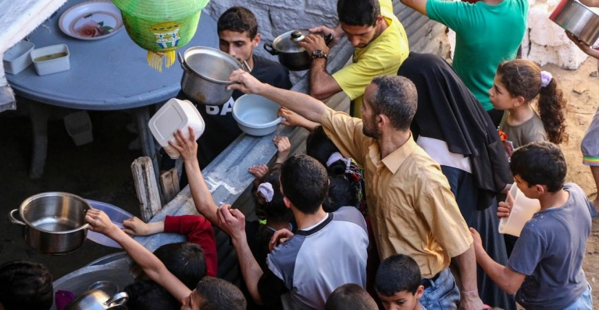 """""""الغلابة"""" يتوافدون لملء صحونهم من وجبات الطباخ في غزة"""