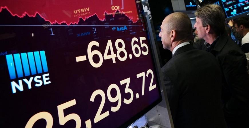 متداولون في بورصة نيويورك أثناء متابعة تراجع الأسهم الأميركية (أ.ب)