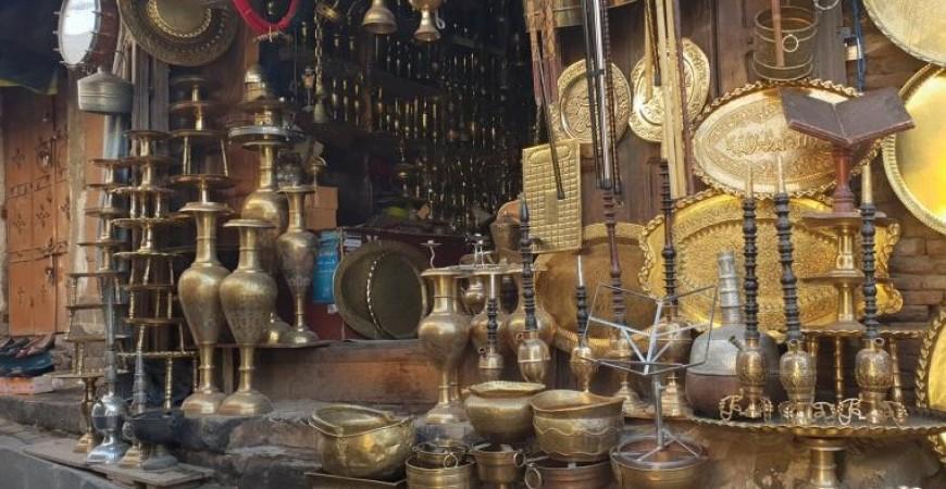 إبراهيم الأنسي أحد البائعين بالأسواق الحرفية في صنعاء القديمة فرح بشهر رمضان، لتحسن بيع الأدوات النحاسية (الجزيرة)