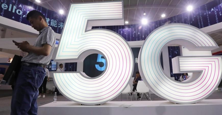 رجل يقف إلى جانب إعلان ضخم لتكنولوجيا الاتصالات 5G في معرض تينسنت العالمي في منطقة يونان الصينية 23 مايو 2019 (رويترز)