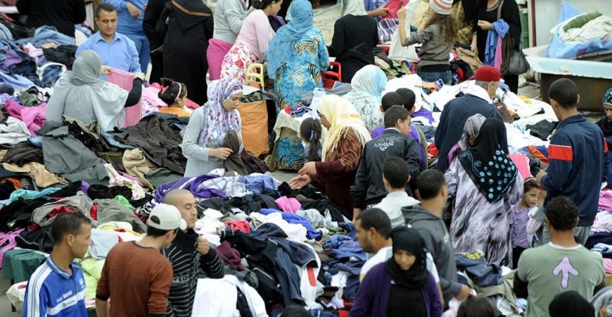 تونسيون يشترون الثياب في سوق في العاصمة تونس (أ.ف.ب)